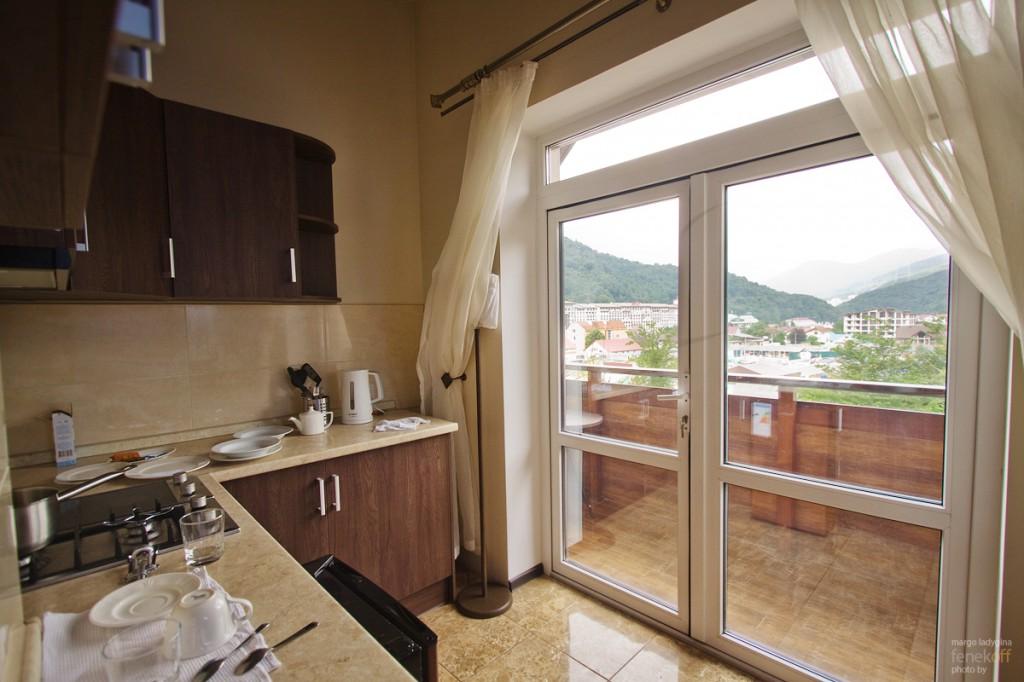 Кухня и балкон с видом на горы в отеле Горная резиденция
